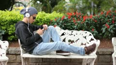 Boy listening music on mobile phone with earphone Stock Footage