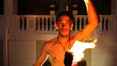 Medium shot of young Fire Dancer makes acrobatics with fire to camera Stock Footage