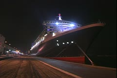Queen Mary 2 ocean liner, alongside the pier at Rio de Janerio at night Stock Footage