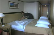Queen Mary 2 ocean liner, stewardess makes up cabin, makes bed Stock Footage