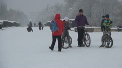 Children with Bikes in Snow in Park, Father and Son Playing Football in Snow - stock footage