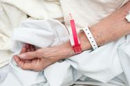 Stock Photo of elderly woman wearing medical arm bands
