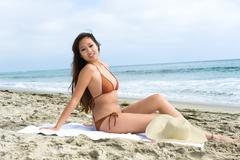 Asian woman sunbathing at the beach Stock Photos
