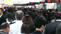 Commuting passengers walk through busy train station at rush hour in Tokyo Stock Footage