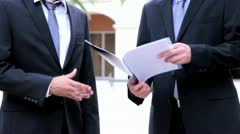 Businessman showing a file to his colleague Stock Footage