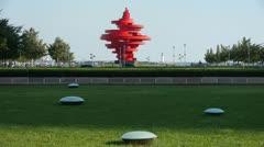 Red torch sculpture,Green grass & Seaside lighthouse. Stock Footage