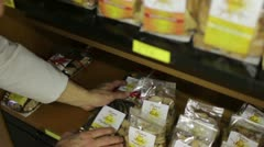 Pastry chef puts packets of cookies on the shelves Stock Footage