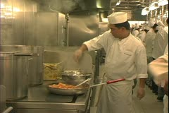 Queen Mary 2 ocean liner, galley, kitchen, chefs with skillets and ladles Stock Footage