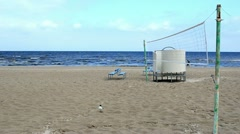 Seaside beach volleyball net blue benches people walk seagull Stock Footage