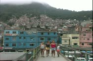 Stock Video Footage of Rio de Janerio, Brazil, favelas, huge slums, wide shot, people walk on bridge