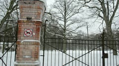Locked retro steel park gates winter people walk snow Stock Footage