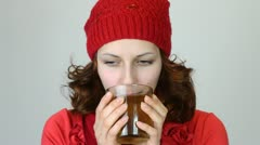 Pretty girl in a red cap drinking tea Stock Footage