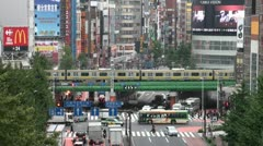 Tokyo Shinjuku crossing commuter trains cars traffic pedestrians Japan - stock footage