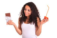 young woman holding orange and chocolate. isolated over white. isolated over  - stock photo