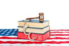 gavel, books and handcuffs on american flag - stock photo