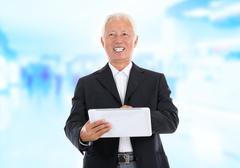 Asian senior businessman using tablet-pc Stock Photos