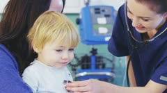 Cute little boy sitting on his mothers lap is being examined by a female nurse Stock Footage