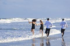 four young people, two couples, having fun on a beach - stock photo