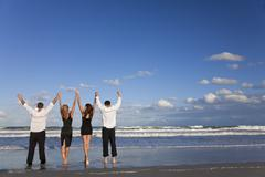 four young people, two couples, arms up celebrating on beach - stock photo