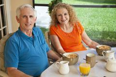 Senior man and woman couple enjoying a healthy breakfast Stock Photos