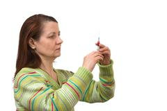 Woman looks at a syringe Stock Photos