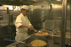 Queen Mary 2 ocean liner, galley, kitchen, chefs with giant skillet, potatoes Stock Footage