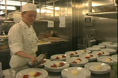 Queen Mary 2 ocean liner, galley, kitchen, chefs plating deserts - stock footage