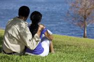 Stock Photo of rear view of african american couple sitting by lake
