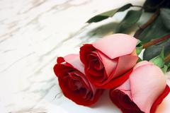 three roses on a marble table - stock photo