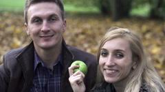 Onnellinen pari rakastunut istuu syksyllä puistossa, hidastettuna, ampui 240fps Arkistovideo
