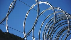 Razor Wire Close Up Pan Against a Blue Sky - stock footage