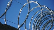 Stock Video Footage of Razor Wire Close Up Pan Against a Blue Sky