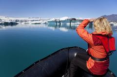 woman explorer using boat in iceberg field, jokulsarlon lagoon, iceland - stock photo