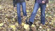 Couple kicking leaves in autumn park, slow motion, shot at 240fps HD Stock Footage