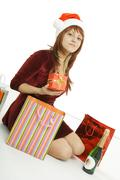 the girl in a christmas cap with purchases - stock photo