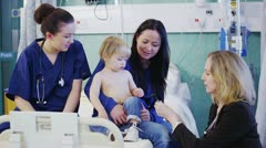 Cute little boy sitting on his mothers lap is being examined by medical staff Stock Footage