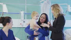 Cute little boy in his mothers arms doesn't want to be examined by the doctor Stock Footage