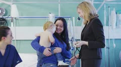 Cute little boy in his mothers arms being examined by a female doctor Stock Footage