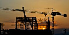 silhouette crane building and sunset of southeast asia - stock photo