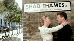 Just married couple kissing against a wall under a London city sign Stock Footage