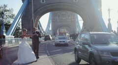 Just married couple dancing on London Bridge among passersby Stock Footage