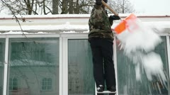 Man camouflage ladder orange shovel tool clean snow roof winter Stock Footage