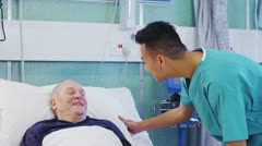 Male nurse at the bedside of an elderly male patient Stock Footage