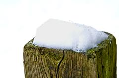 snow on fence post - stock photo