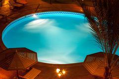 nighttime setting of a luxury villa poolside - stock photo