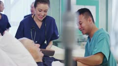 One male and one female nurse at the bedside of an elderly male patient Stock Footage