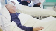 Elderly patient rests as a doctor and consultant discuss another patient.  Stock Footage