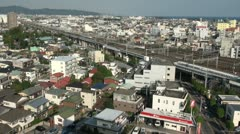 Shinkansen train leaves station with city overview in Japan Stock Footage