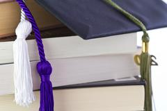 graduation cap and tassles with school items - stock photo