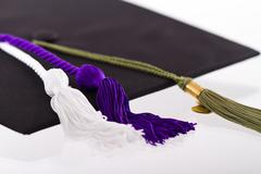 Graduation cap and tassles with school items Stock Photos